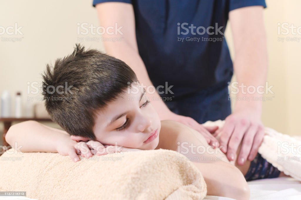 Close up A little boy relaxes from a therapeutic massage. Male...