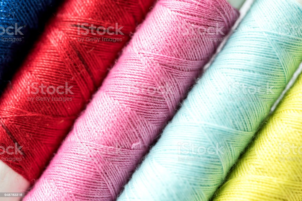 Close up a multi color of bobbins threads roll as background stock photo