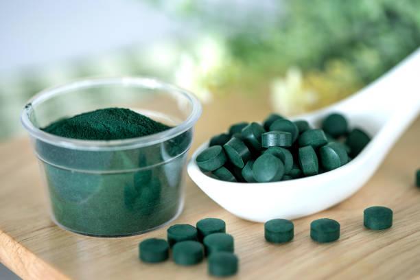 Schließen Sie ein Spirulina Pulver und Spirulina Pillen in Löffel, gesunde Superfood-Diät und ein Entgiftungs-Ernährungskonzept – Foto