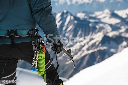 istock Close up A young guy climber holds in his hand an ice-ax standing on a summit high in the mountains. Extreme sport concept 828144150