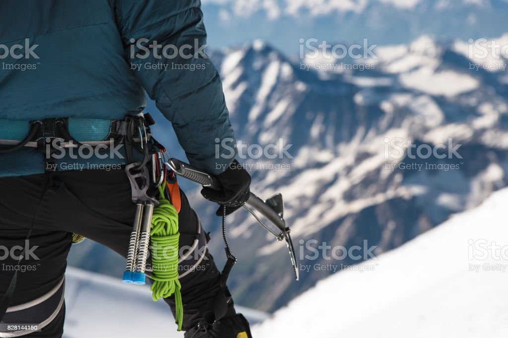 Close up A young guy climber holds in his hand an ice-ax standing on a summit high in the mountains. Extreme sport concept stock photo