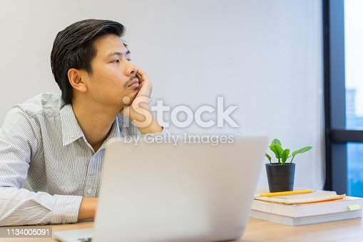 istock close up adult asian employee man feeling bored and sleepy at desktop in the after noon after have lunch, lifestyle concept 1134005091