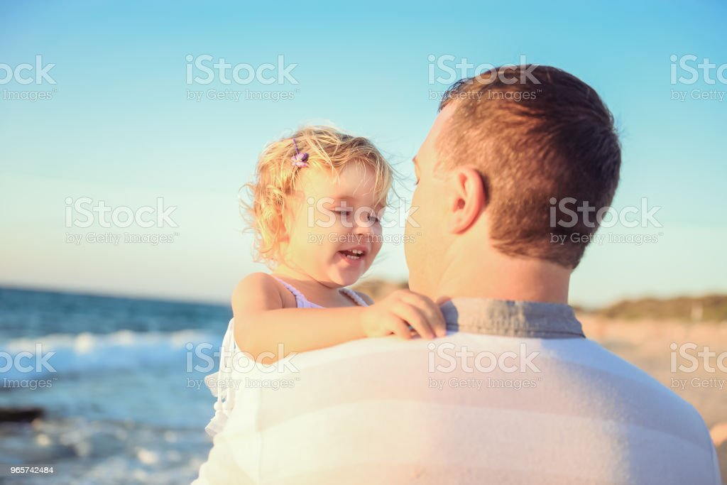 Close up adult father holding his happy blondy child girl daughter on the hands and having fun walking on the beach. Family vacation, travel concept. Bright sunlight. Selective focus. Copy space. - Royalty-free Adult Stock Photo