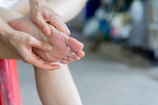 close up adult woman hand holding foot to massing after feeling pain from gout symptoms for healthy life concept