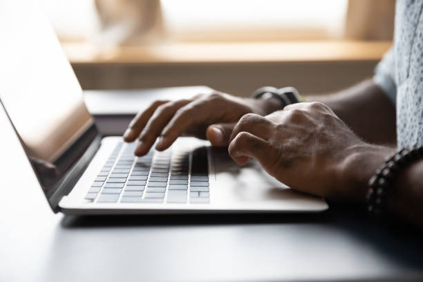 Close up African American male hands typing on laptop keyboard stock photo