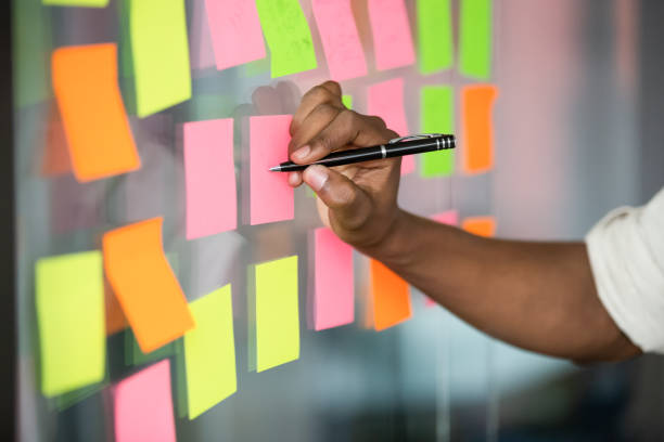 close up african american manager writing notes on kanban board. - post it foto e immagini stock