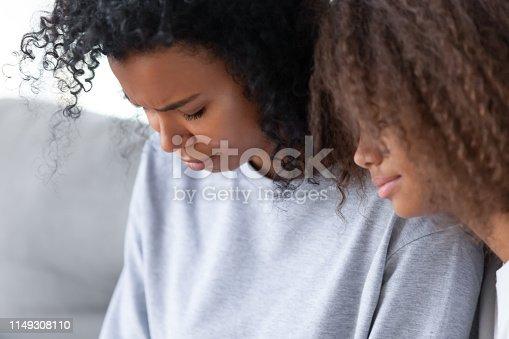 1135353632 istock photo Close up African American teen daughter hugging upset depressed mother 1149308110