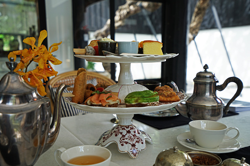 Smoked salmon and avocado on toast ,assorted fruits ,scone ,butter pound cake ,chocolate fudge brownie and fried springrolls served with teapots