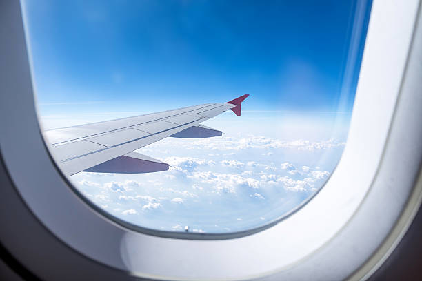 Close up Airplane window with airplane wing stock photo