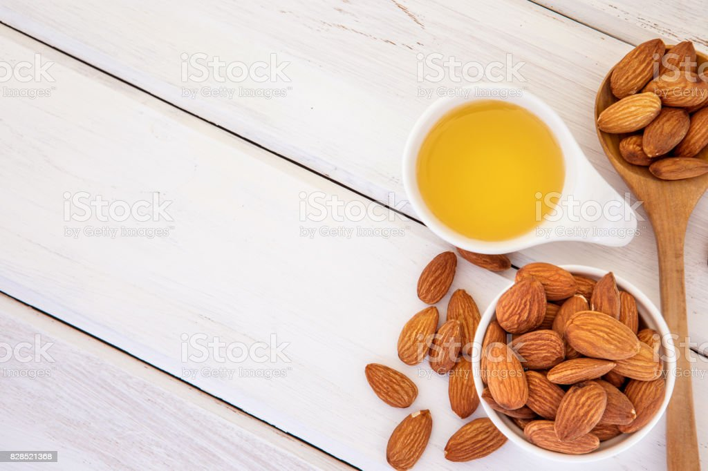 Close up almond oil in the bottle and almond seed in white cup for oil massage and spa treatment ingredient on the white wooden table background , top view or over head shot with copy space stock photo