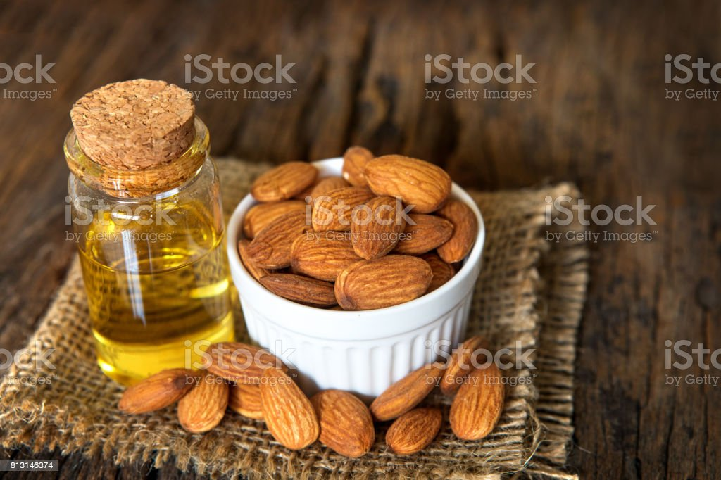 Close up almond oil in the bottle and the  almond seed in white cup for oil massage and spa treatment ingredient on wooden table background stock photo