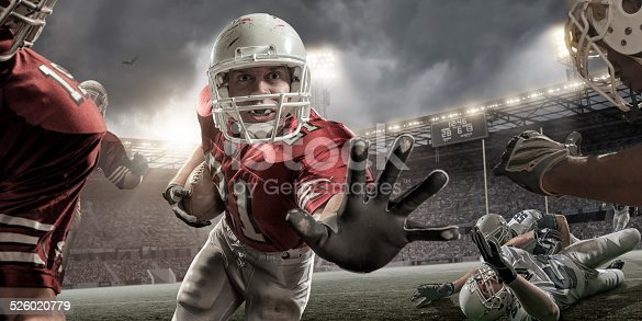 Close up image of a professional American football player holding football and running with outstretched hand towards camera during American football game. Action is set in a generic outdoor floodlit American football stadium full of spectators under stormy evening sky. Players are wearing generic unbranded kit. Stadium advertising is fake.