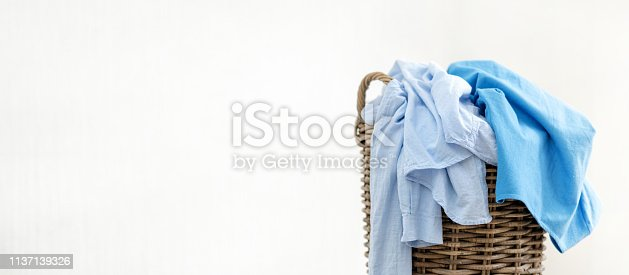 istock Close up and long photo of laundry basket with pastel blue shirt and dress isolated inside apartment with light interior and copy space for text 1137139326