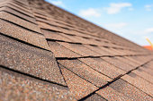 Close up and selective focus photo of asphalt shingle or tile on roof of new house under construction against blue sky
