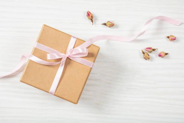 hautnah und draufsicht beige handwerk geschenkbox mit rosa seidig band auf einem hölzernen hintergrund, textfreiraum. - geschenk zur taufe stock-fotos und bilder