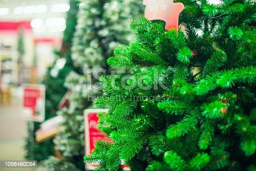 Close up artificial green Christmas trees for sale in the market, shop. Prepearing for Christmas eve, new year party. Selective focus, copy space