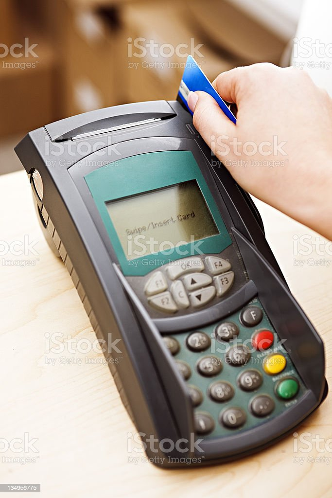 Close up as woman's hand swipes credit card through reader. stock photo