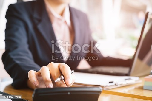 istock Close up asian business woman using a calculator to calculate the numbers.Business finances and accounting concept 1044572780
