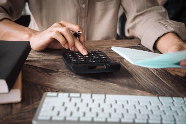 close up asian business woman using a calculator to calculate the numbers.business finances and accounting concept - calcolare foto e immagini stock
