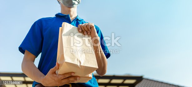 Close up Asian Delivery man wearing mask send food from restaurant protection pandemic and fever on front receiver shipping deliver cargo social distancing while the virus is spreading.