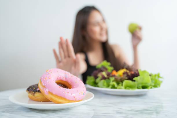 Cerrar las mujeres de dieta asiática usando la mano empujar hacia fuera sus donuts favoritos y elegir la manzana verde y verduras para la buena salud. dieta y el concepto de atención médica. - foto de stock