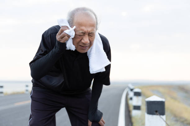 Close up Asian elderly wiping sweat with towel after exercised running on road in the morning sunshine. health lifestyle and exercise Concept. stock photo
