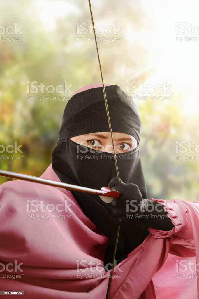 Close up asian muslim woman with bow ready to shoot an arrow royalty-free stock photo