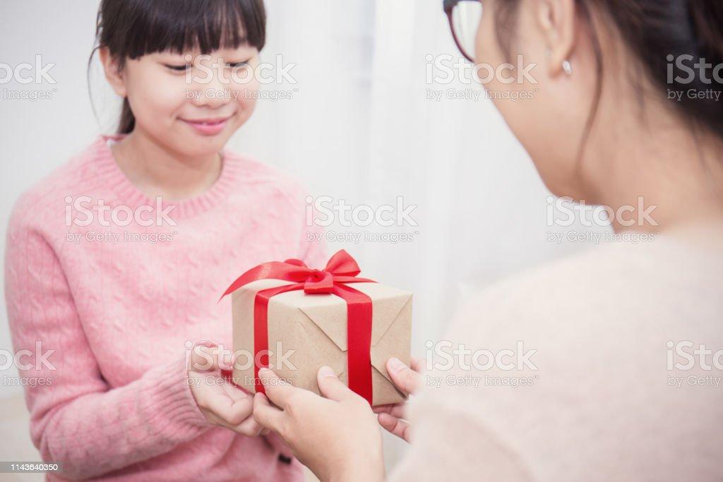 クローズアップアジアの十代の少女は、ギフトボックスで彼女の母親を驚かせます.ボクシングデーホリデーバースデークリスマスと motherâs のコンセプト。 ストックフォト