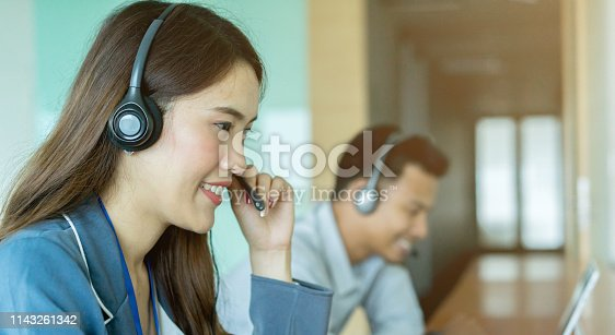 1142008983 istock photo close up asian woman call center agent wear headset device and smiling working in operation room with service-mind at  desktop table , telemarketing and help desk concept 1143261342