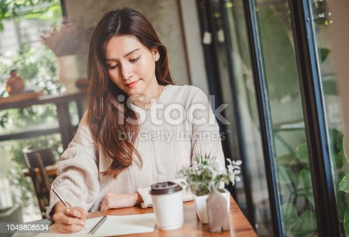 1147767708 istock photo Close up Asian woman hand writing on notebook 1049808534