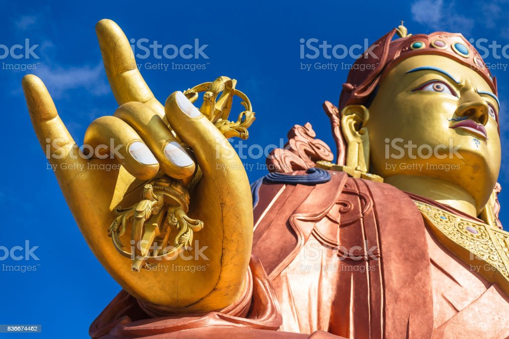 Close up at the right golden hand with mace and head of Guru Rinpoche statue, the patron saint of Sikkim in Guru Rinpoche Temple at Namchi. Sikkim, India. stock photo
