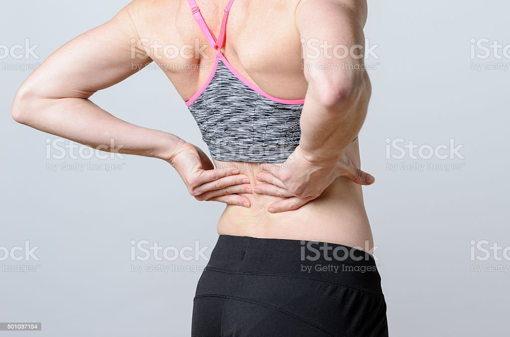 Close up Athletic Woman Holding her Injured Back stock photo