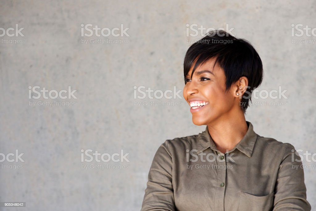 Close up attractive young african woman looking away and smiling stock photo