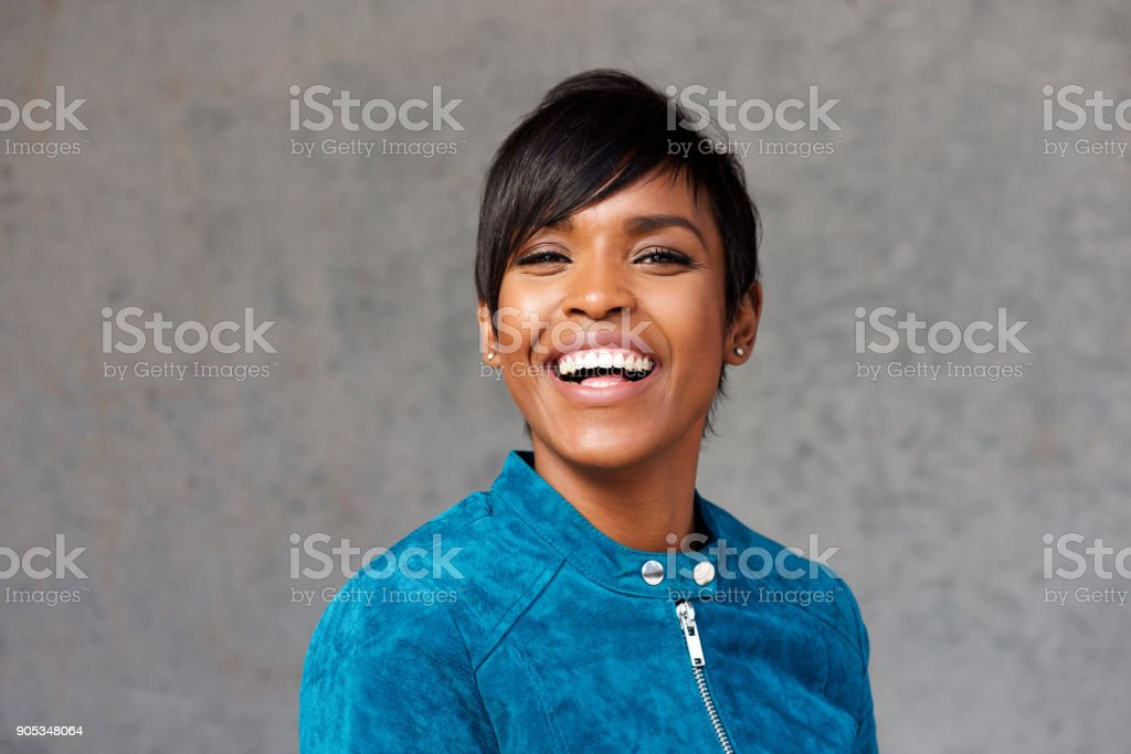 Close up attractive young black woman laughing against gray wall stock photo