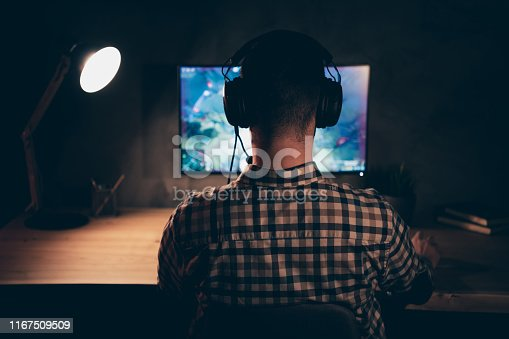 Close up back rear behind view photo he him his guy play videogame, battle challenge participation talk teammates headset microphone wear casual plaid checkered shirt internet table house indoors