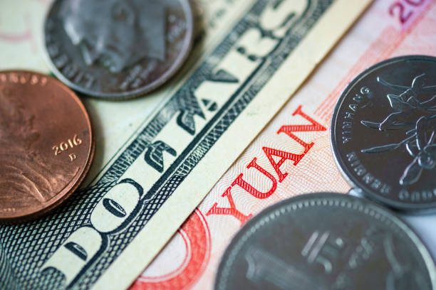 Close up banknote and coins of US dollar and Yuan which its are the biggest economic in the world. Trade war and tax barrier concept. Close up banknote and coins of US dollar and Yuan which its are the biggest economic in the world. Trade war and tax barrier concept. trade war stock pictures, royalty-free photos & images