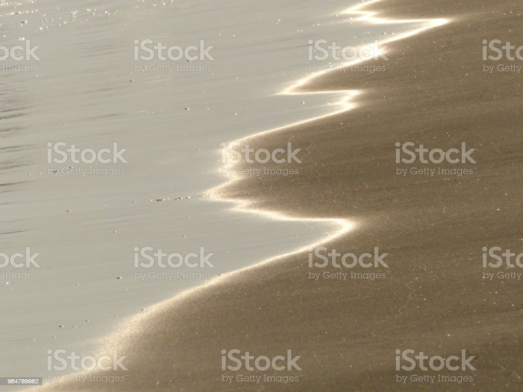 Close up beach with sunset reflected on surface. royalty-free stock photo