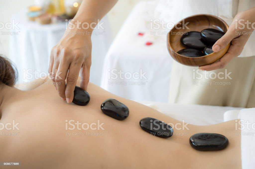 close up beautiful and healthy woman  during a back stone therapy massage in spa salon stock photo
