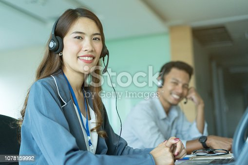 1142008983 istock photo close up beautiful asian woman call center wear headset device working on laptop with colleagues in the day shift at operation room , telemarketing and help desk concept 1078159992