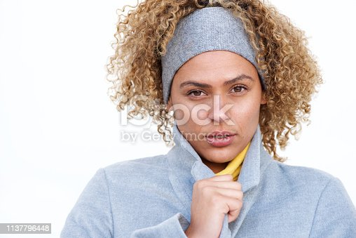 910856488 istock photo Close up beautiful young african american woman with winter coat and headband by white background 1137796448
