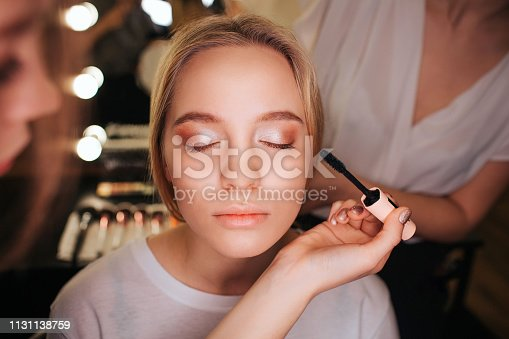 istock Close up beautiful young blonde woman face. She has eyeshadows on eyeline. Make up artist use mascara. Hairdresser work behind. 1131138759
