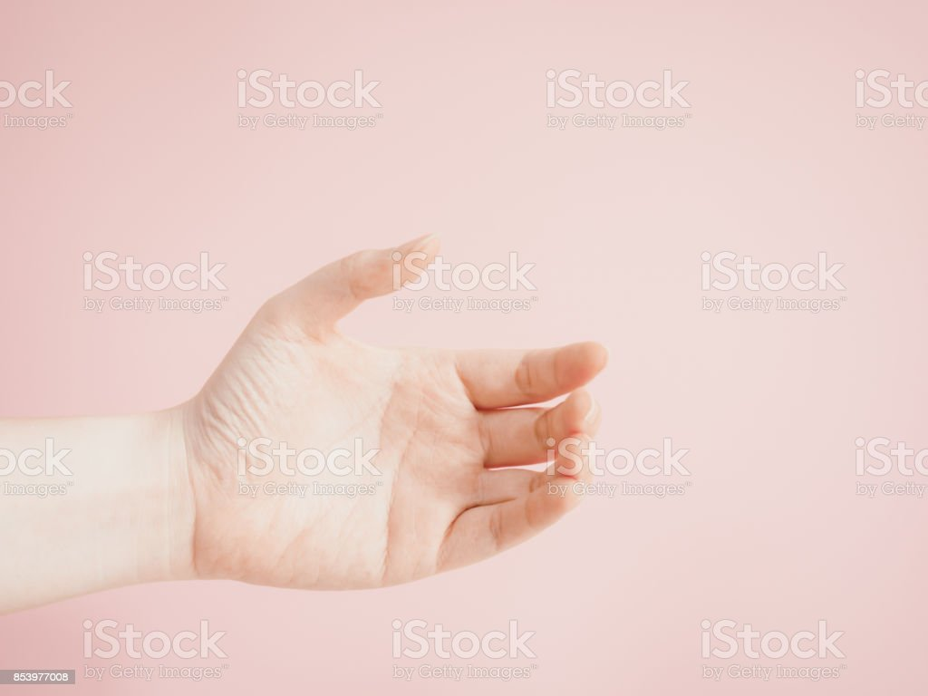 close up beauty woman left hand show signal look like hold something with pink pastel background stock photo