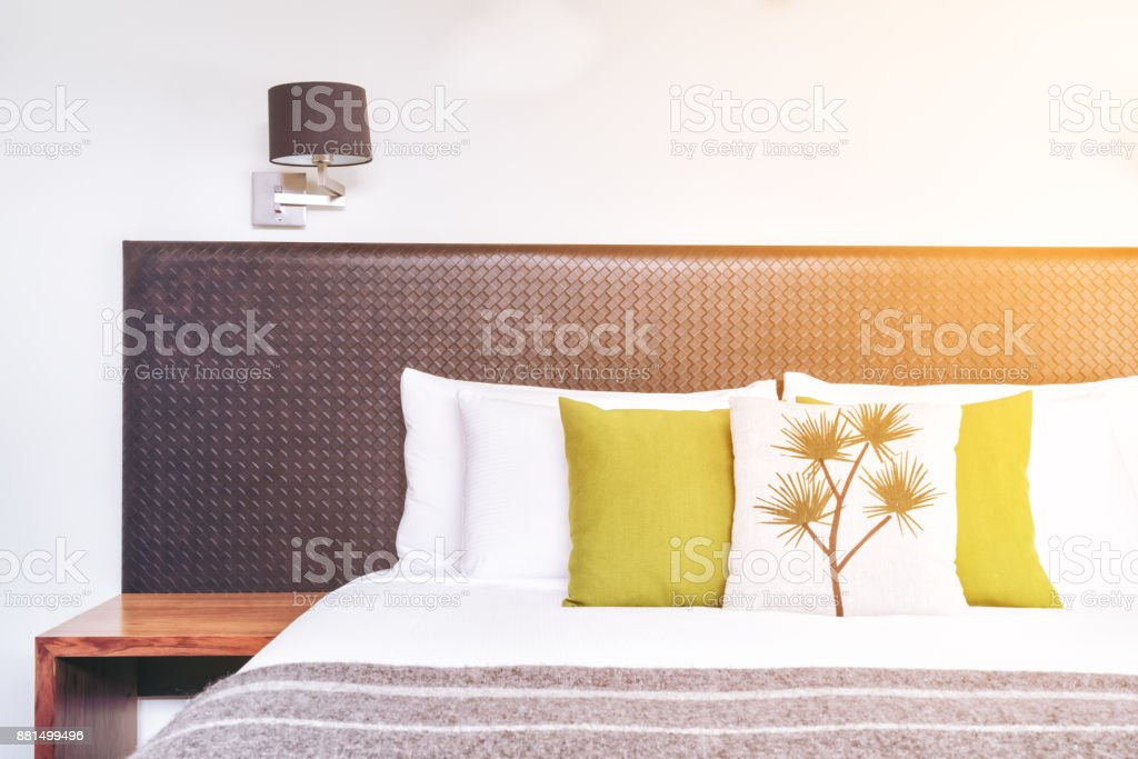 Bed headboard design in bedroom interior with pillows and blanket on...