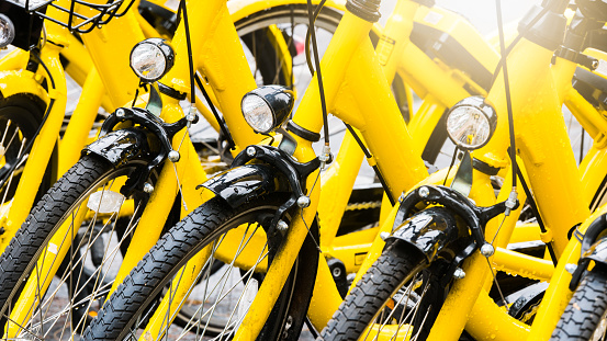Close up Bicycle headlights on group of yellow vintage bike parking in the Park to service the touristi n bike sharing concept.