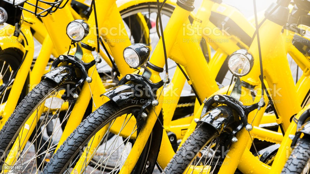 Close up Bicycle headlights on group of yellow vintage bike parking in the Park to service the touristi n bike sharing concept. stock photo