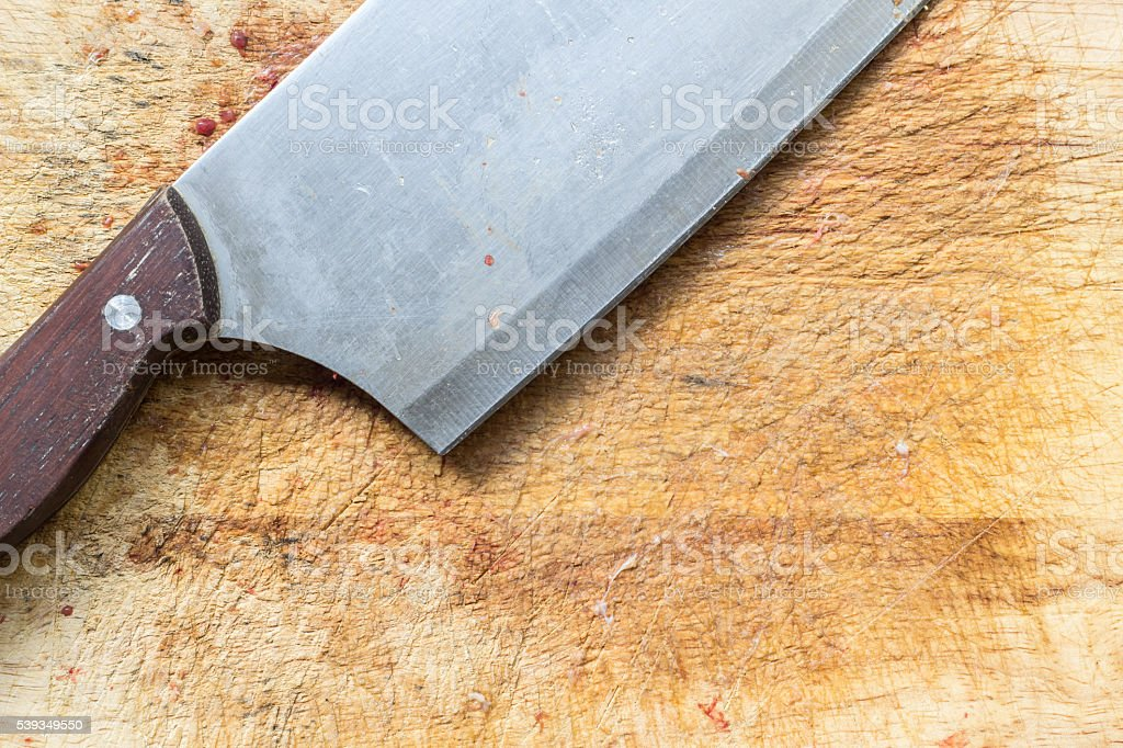 Close up big knife on rought wooden chopping block stock photo