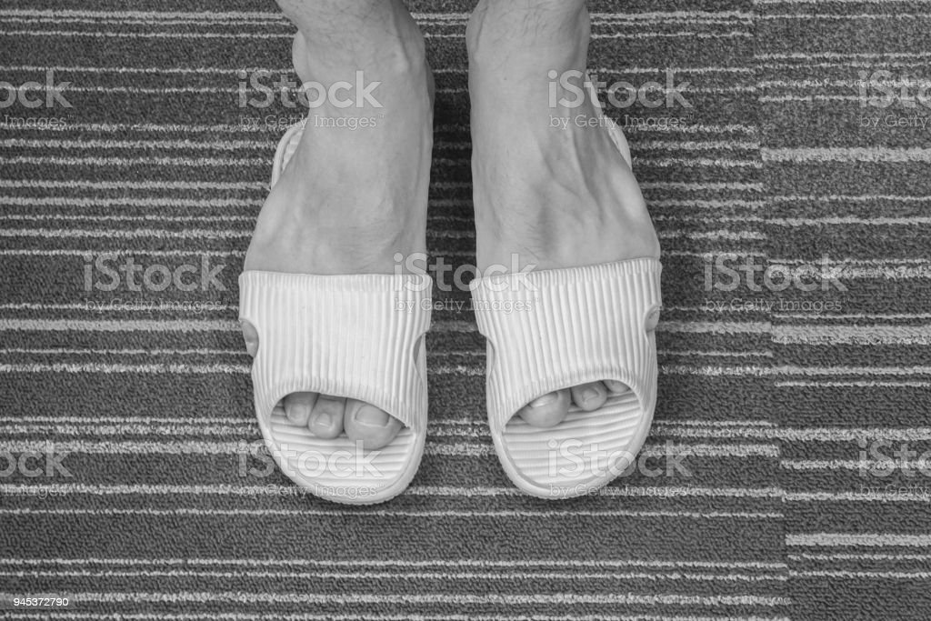 close up black and white men wear too tight sandal on his feet in the house stock photo