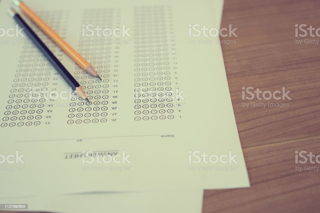 Close Up Black And Yellow Pencil Over Exam Answer Sheet