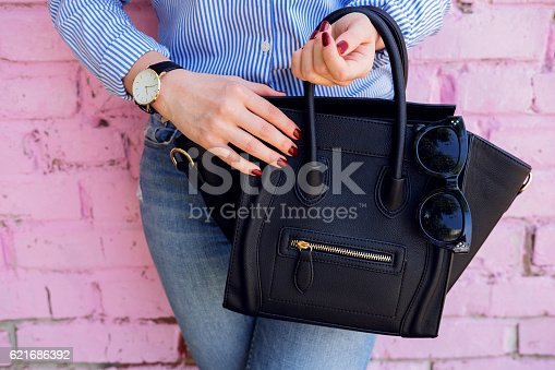 istock Close up black leather bag in hand of fashion woman. 621686392