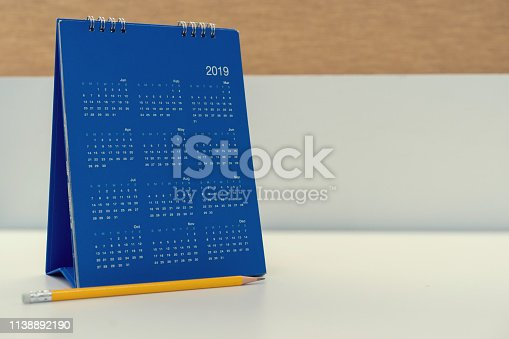 istock close up blue color calendar 2019  standing on white table at office room for make appointment or remind important date , workplace with object concept 1138892190